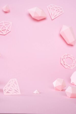 A variety of faceted gemstones, made of paper on a pink background. Jewellery concept