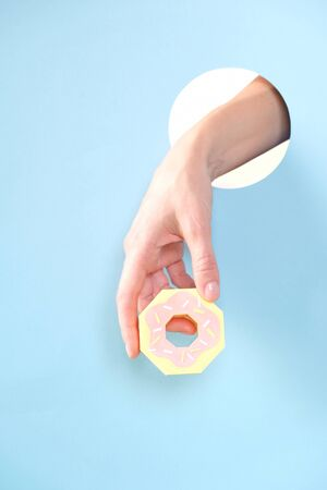 Hello, August. Close up of human hand protruding through hole in blue background, holding paper donut.