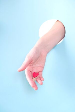 be mine valentine. Close up of human hand protruding through hole in blue background, holding red small heart.