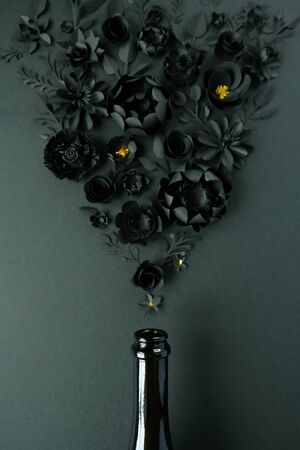 Champagne bottle with different black paper flower on black background. Stock Photo