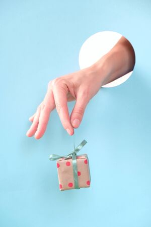 Close up of human hand protruding through hole in blue background, holding red small gift.
