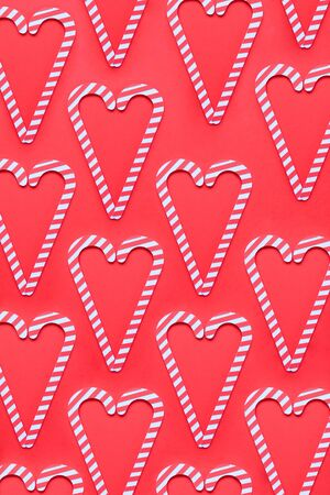 Christmas seamless pattern. Red colors. Candy canes and on red background