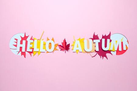 Lettering hello autumn with leaves of paper fall red, orange, yellow leaf fall. Pink background. Handmade origami.