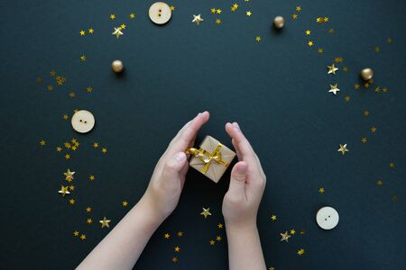 Christmas or New Year. Childrens hands holding a Christmas gift. The concept of giving. Gold decoration on black background colorful glass balls on black background.