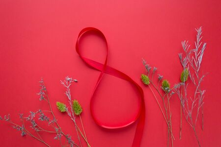 Figure 8 made of red ribbon with flowers on red background