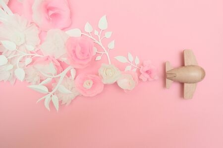 Travel concept with wood plane and paper flowers, petals on pink background.. Top view, flat lay. Copy space. Trip, vacation concept. Stok Fotoğraf