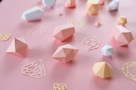 A variety of faceted gemstones, made of paper on a pink background. Jewellery concept Stok Fotoğraf - 130058567