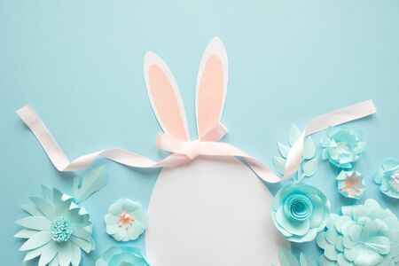 Happy Easter. Easter egg made of paper with different paper flowers on blue background.