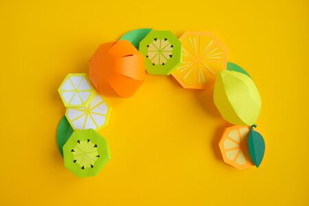 Fruit made of paper. Yellow background. Theres room for writing. Tropics. Lemon, orange and kiwi. 写真素材