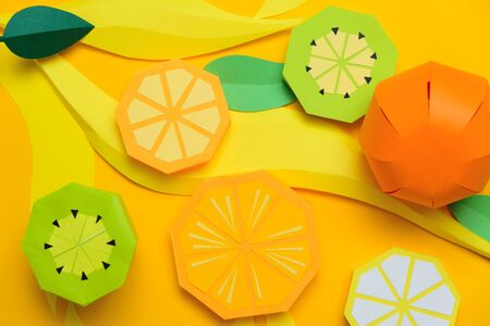 Fruit made of paper. Yellow background. Theres room for writing. Tropics. Lemon, orange and kiwi. Stok Fotoğraf