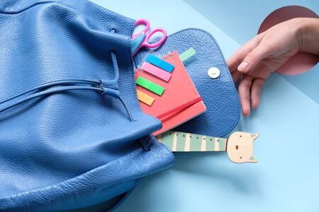 Hand holding backpack with different colorful stationery on blue table. Back to school concept. Trend hole Stok Fotoğraf