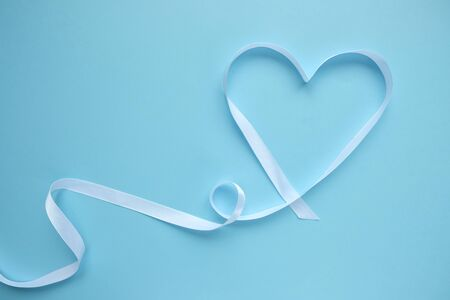 white ribbon in the shape of a heart on a blue background