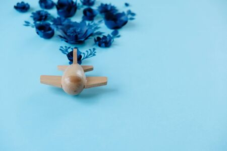 wooden toy airplane lucky blue flower cut from paper. The concept of spring and travel