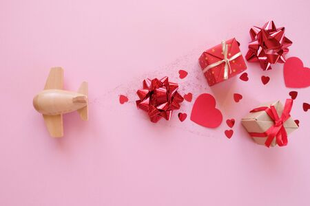 A small wooden toy airplane carries Valentine's elements. Vapor trail of sequins in the shape of heart, gifts, bow and red glitter. Valentine's day Stok Fotoğraf