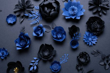 Black and blue paper flowers on black background. Cut from paper.