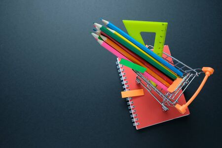 Back to school. Multicolored pencils and other supplies in shopping cart on black background