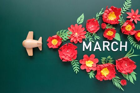Hello, March. Wooden toy airplane lucky red flower cut from paper. The concept of spring and travel Stok Fotoğraf