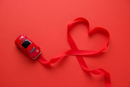 Red car toy carries Valentine's ribbon. Red ribbon in the shape of heart. Valentine's day Reklamní fotografie
