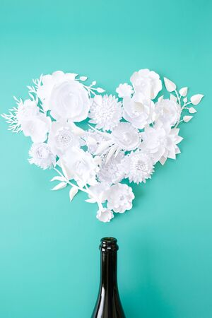 Flowers in the shape heart with bottle on neo-mint background.