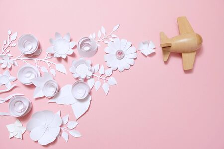 wooden toy airplane lucky white flower cut from paper. The concept of spring and travel