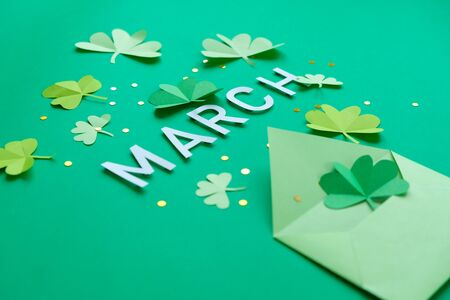 St. Patrick's day, pattern of clovers cut out of paper on a green shiny background