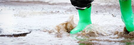 child with green rain boots jumps into a puddle. Long format for web