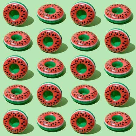 Red inflatable watermelons on a green background. Trendy modern pattern Фото со стока