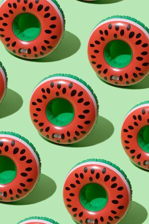 Red inflatable watermelons on a green background. Trendy modern pattern Stok Fotoğraf