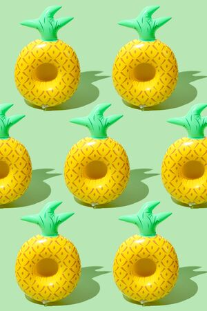 Yellow inflatable pineapples on a green background. Trendy modern pattern Stok Fotoğraf