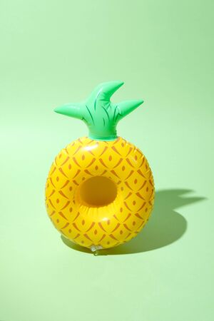 Yellow inflatable pineapples on a green background. Trendy modern element Stok Fotoğraf