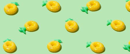 Yellow inflatable pineapples on a green background. Trendy modern pattern Фото со стока