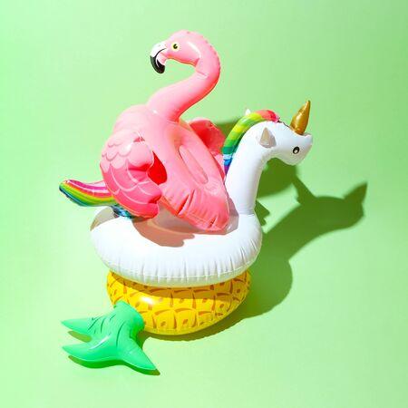 Hello, summer Unicorn, flamingo and pineapple swim tube on green background. Inflatable unicorn, flamingo and pineapple. Fantasy Swim Ring for Summer Pool Trip