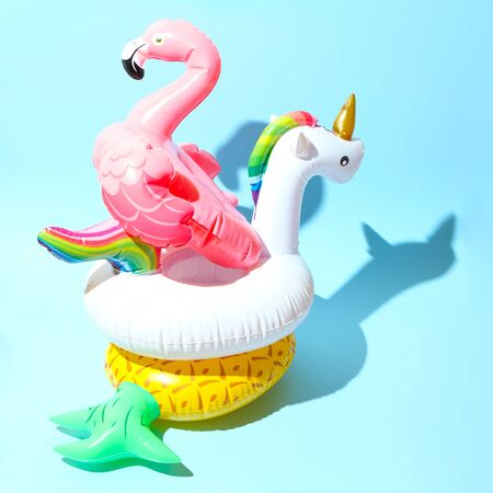 Unicorn, flamingo and pineapple swim tube on blue background. Inflatable unicorn, flamingo and pineapple. Fantasy Swim Ring for Summer Pool Trip
