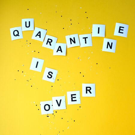 Lettering from paper. The inscription quarantine is over on a yellow background