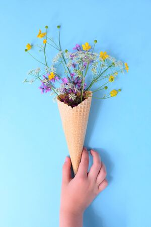 HAnd hold bouquet of wild flowers in a waffle cone. Summer concept. Flat lay.