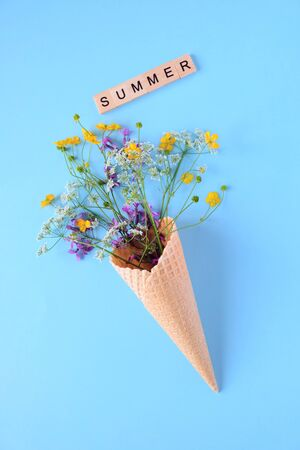 Bouquet of wild flowers in a waffle cone. Summer concept.