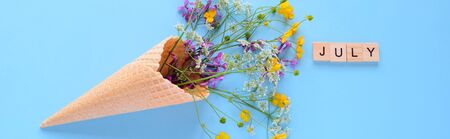 Bouquet of wild flowers in a waffle cone. Summer concept. Flat lay. hello, july