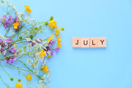Bouquet of wild flowers on blue background. Hello july. inscription made of wooden cubes Фото со стока