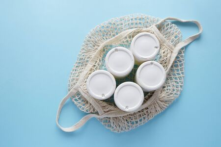 Homemade pot of Greek yogurt in glass jars in a string bag on a light blue background. Selective focus, copy space.