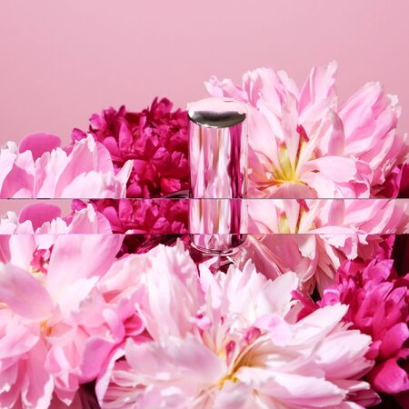 Perfume bottle in front of pink flowers on pink background Фото со стока