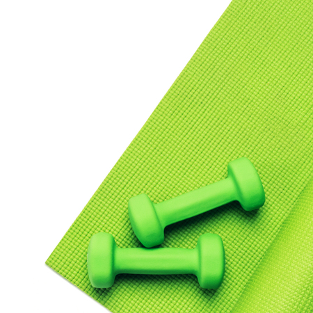 Fitness concept - green yoga mat and dumbbells on the white background Stock Photo