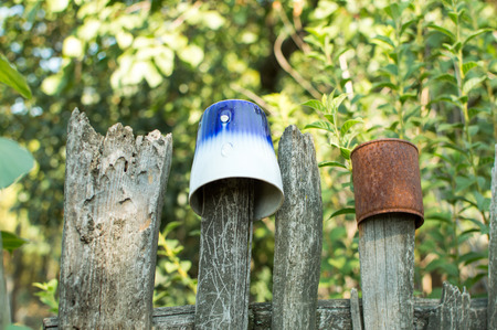 Broken old cup on the wooden fence