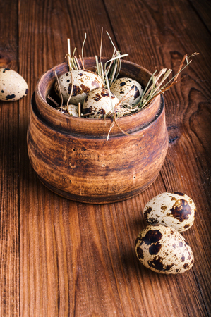 Quail eggs in a wooden bowl on a background.
