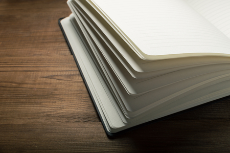 memoir: White pages of notepad on the wooden table.