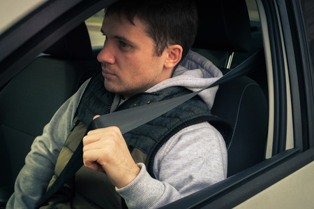 fastens: Driving safety. A young man fastens the seat belt. Stock Photo