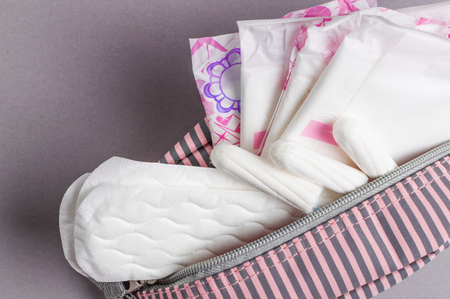 Menstrual tampons and pads in cosmetic bag. Menstruation cycle. Hygiene and protection.