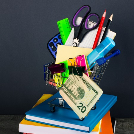 single word: Shopping cart with school supplies. Back to school. Stock Photo