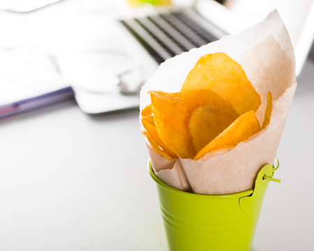Unhealthy chips for snack at work. Food in the office.