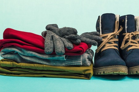 Woman clothes and boots on a blue background. Winter concept. Stock Photo