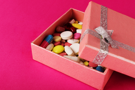 Gift box with pills on a pink backgroung. Medicine present concept.